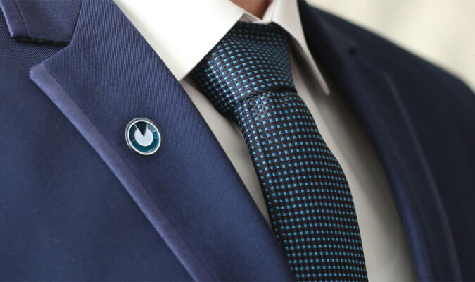 Man wearing business suit, with Vestmark logo pinned to his lapel